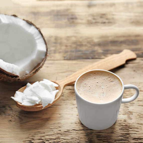 Cup of tasty coconut coffee and spoon with butter on wooden tabl
